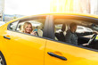 canvas print picture - Photo of young blonde with phone in her hand sitting in back seat of yellow taxi with driver.