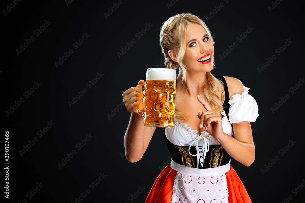 Fototapeta Smiling young sexy oktoberfest girl waitress, wearing a traditional Bavarian or german dirndl, serving big beer mug with drink isolated on black background.