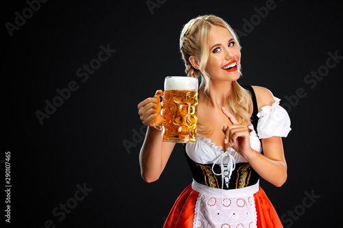 Door stickers Equestrian Smiling young sexy oktoberfest girl waitress, wearing a traditional Bavarian or german dirndl, serving big beer mug with drink isolated on black background.