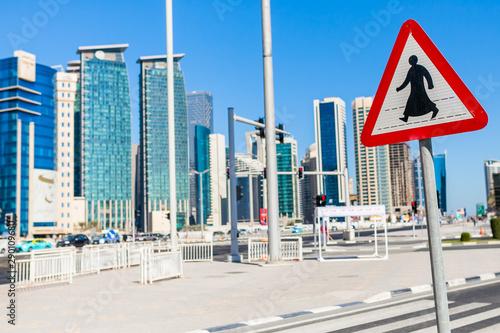 Znak przejście dla pieszych na tle wieżowców w Qatarze, znak w kraju arabskim - fototapety na wymiar