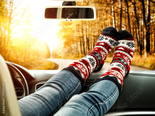 Stickers pour portes Fleur Woman legs with socks and car interior. Autumn landscape of road and sunny day.