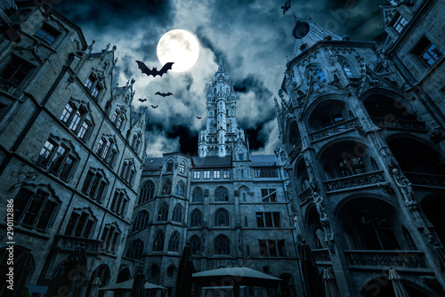 Photo Stands Green blue Marienplatz at night, Munich, Germany. Creepy mystery view of dark Gothic Town Hall with bats. Old spooky castle or palace in full moon. Scary gloomy scene with horror and terror for Halloween theme.