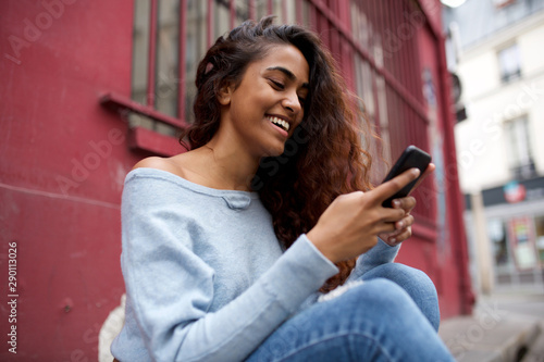 obraz PCV happy Indian girl sitting outside and looking at mobile phone
