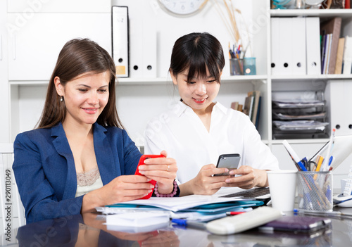 Two businesswomen working with smartphone in the office Tapéta, Fotótapéta
