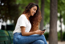 Happy Young Indian Woman Sitting On Park Bench With Cellphone