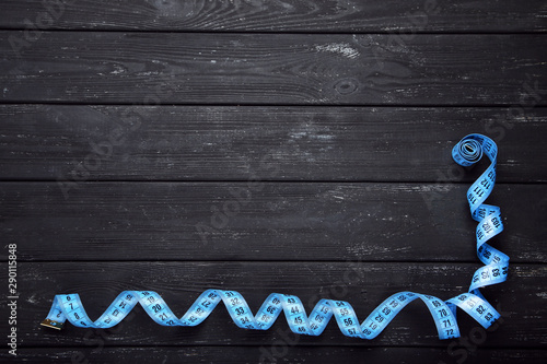 Blue measuring tape on black wooden table
