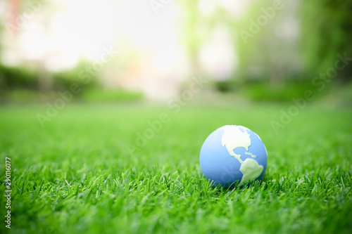 Foto auf AluDibond Lime grun Global Warming, Environment and Ecology Concept. Close up of mini world ball on green grass lawn with rain drop.