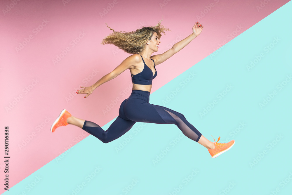 Fototapety, obrazy: beautiful blond-haired woman with fitness lifestyle wearing sportswear is running and jumping with her hair in motion on an isolated background of various colors