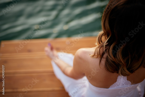 Top view of Caucasian woman sitting on pier in lotus position and meditating. Summer time.