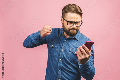 Fotomural Young caucasian man angry, frustrated and furious with his phone, angry with customer service