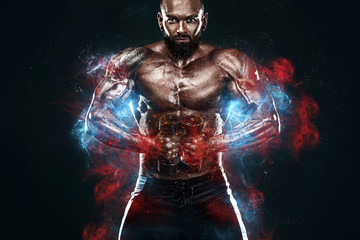 FototapetaStrong and fit man bodybuilder. Sporty muscular guy with dumbbells. Spot and fitness motivation. Man on fire like a phoenix.
