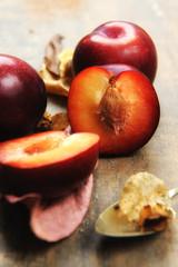 Fototapeta na wymiar Half plum fruit, pitted, unfocused.Second flat, plum, focused.Tasteful.Age wood color background.Close up.No one.
