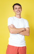 Handsome young man smiling and laughing on yellow background
