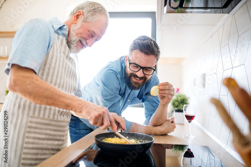 Fotografia  An adult hipster son and senior father indoors at home, cooking.