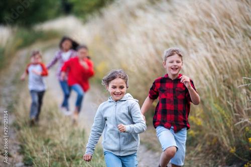 Fotografía  Group of school children running on field trip in nature.