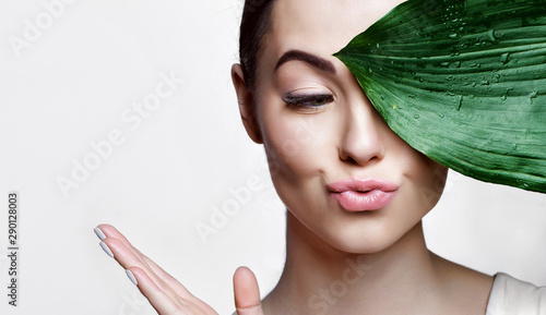 Fototapeta Portrait of young beautiful woman with healthy glow perfect smooth skin holds green tropical leaf. Model with natural nude make up. Gray background. obraz