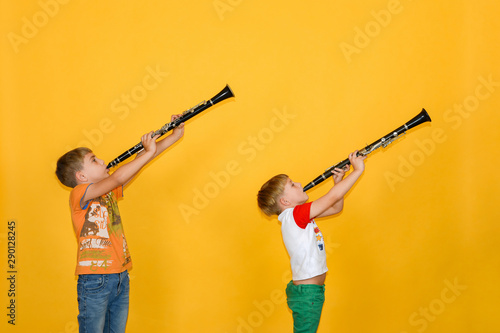 Two boys play the clarinet and hold it up, on a yellow background. - 290128245