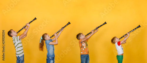 Four people, a musician, stand in a row and play clarinets, photos of childre...