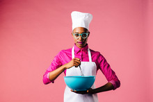 Portrait Of A Young Woman In Cooking Hat And Apron Mixing A Bowl With A Whisker, Isolated On Pink Studio Background