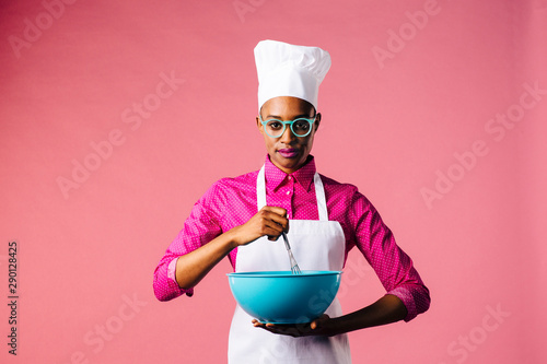 Obraz na plátně  Portrait of a young woman in cooking hat and apron mixing a bowl with a whisker,