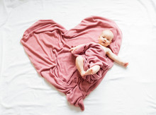 Smiling Baby Lying On A Pink B...