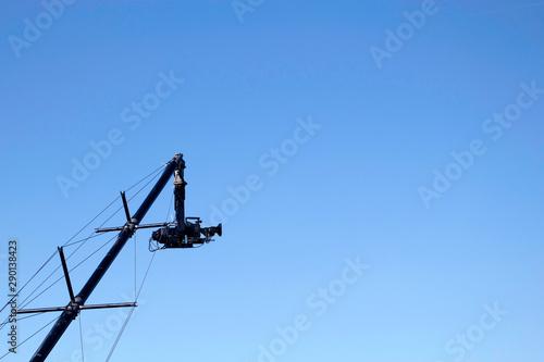 Camera on crane against clear blue sky Wallpaper Mural