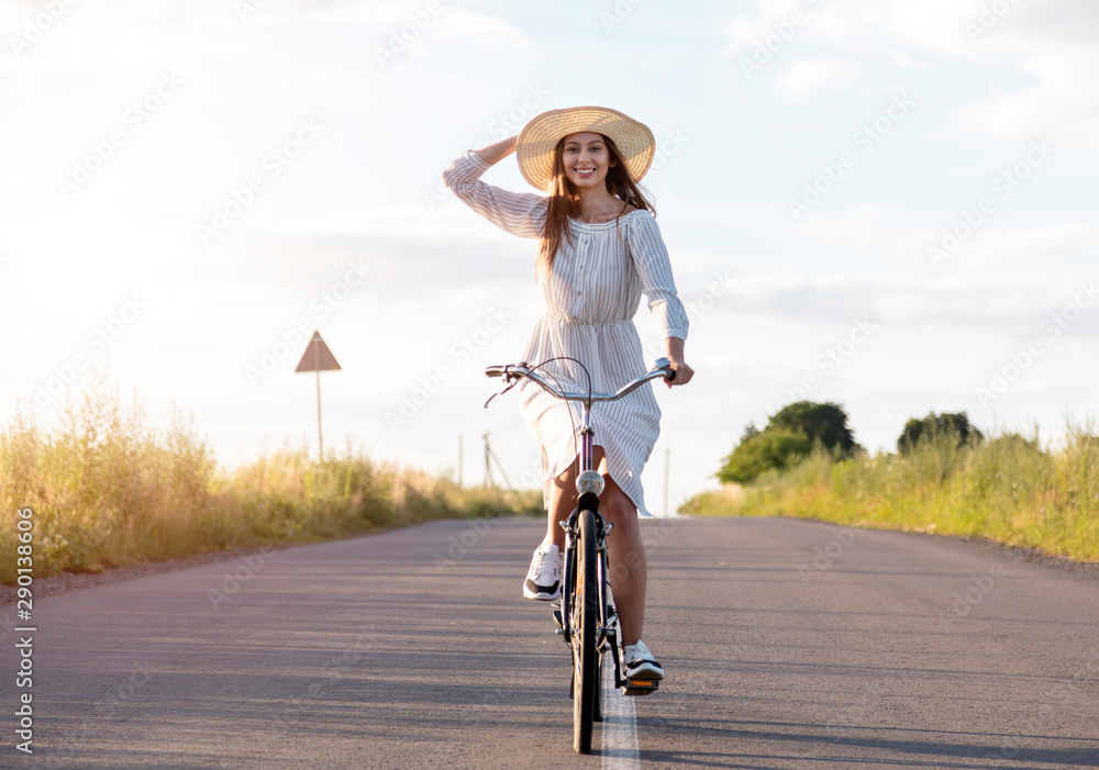 Fototapety, obrazy: Cute female cyclist riding at the camera and smiling while adjusting her straw hat