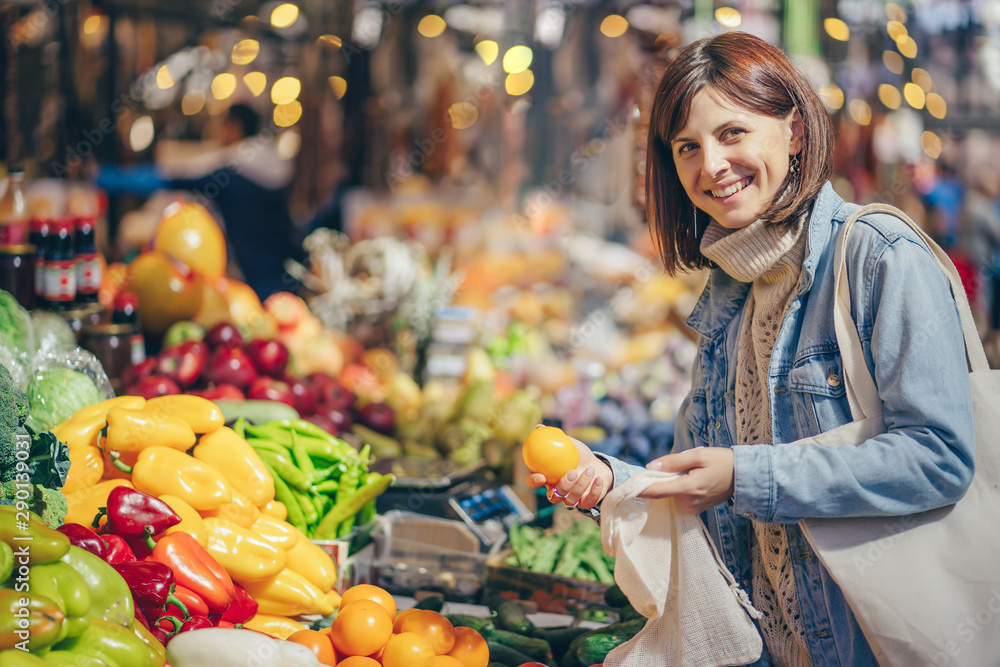 Fototapeta Young Woman puts fruits and vegetables in cotton produce bag at food market. Reusable eco bag for shopping. Sustainable lifestyle. Eco friendly concept.