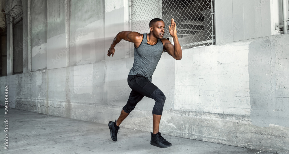 Fototapety, obrazy: African american male athlete sprinter, running at a high speed in urban concrete city background with copy space
