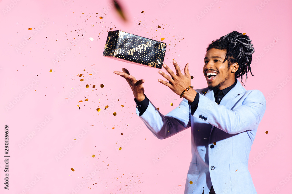 Fototapety, obrazy: Excited man throwing gift in the air amid falling gold confetti