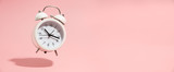 Różowy budzik na pastelowym różowym tle. - 290139871
