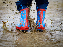 Child Splashes In Muddy Puddle Wearing Wellington Boots