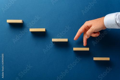 Fotografiet  Businessman walking his fingers up a stairway