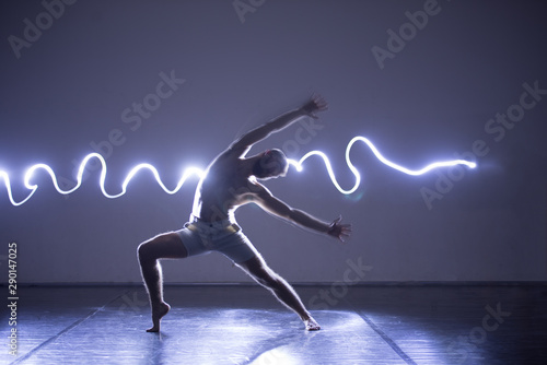 Modern Dance performer dancing with a neon blue light while making gracious moves and spectacular body art expressions.