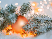 Christmas And New Year Holiday Greeting Card. Beautiful Orange Ball, Pine Branches And A Garland In The Snow. Blurred Yellow Bokeh Background. Shallow Depth Of Field. Toned Image. Copy Space.