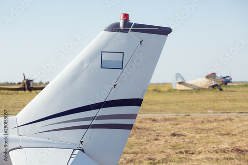 фотография Airplane tail fin - sky with white clouds and old plane in background