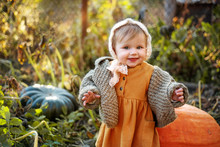 Laughing Adorable Baby Girl With A Pumpkin