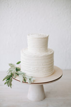 Simple Two Tiered Wedding Cake With Icing And Olive Branch Decoration