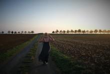 Woman Walking Along A Rural Road, Deux-Sevres, Nouvelle Aquitaine, France