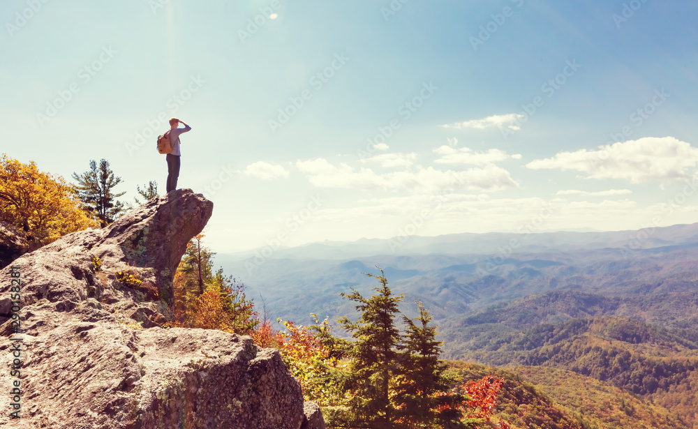 Fototapety, obrazy: Man at the edge of a cliff overlooking the mountains below