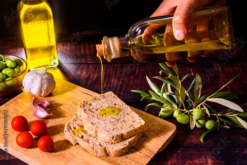 Fototapeta A Mediterranean cook prepares a slice of bread with virgin olive oil, tomatoes and garlic, a traditional breakfast in the Mediterranean countries. obraz