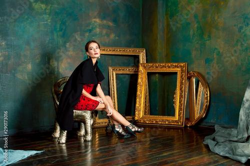 Photo beauty rich brunette woman in luxury interior near empty frames, wearing fashion