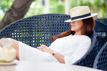 Portrait Image Of A Beautiful Asian Woman With Hat Lying Down And Sleeping On A Bench In The Garden With Coconut On The Table