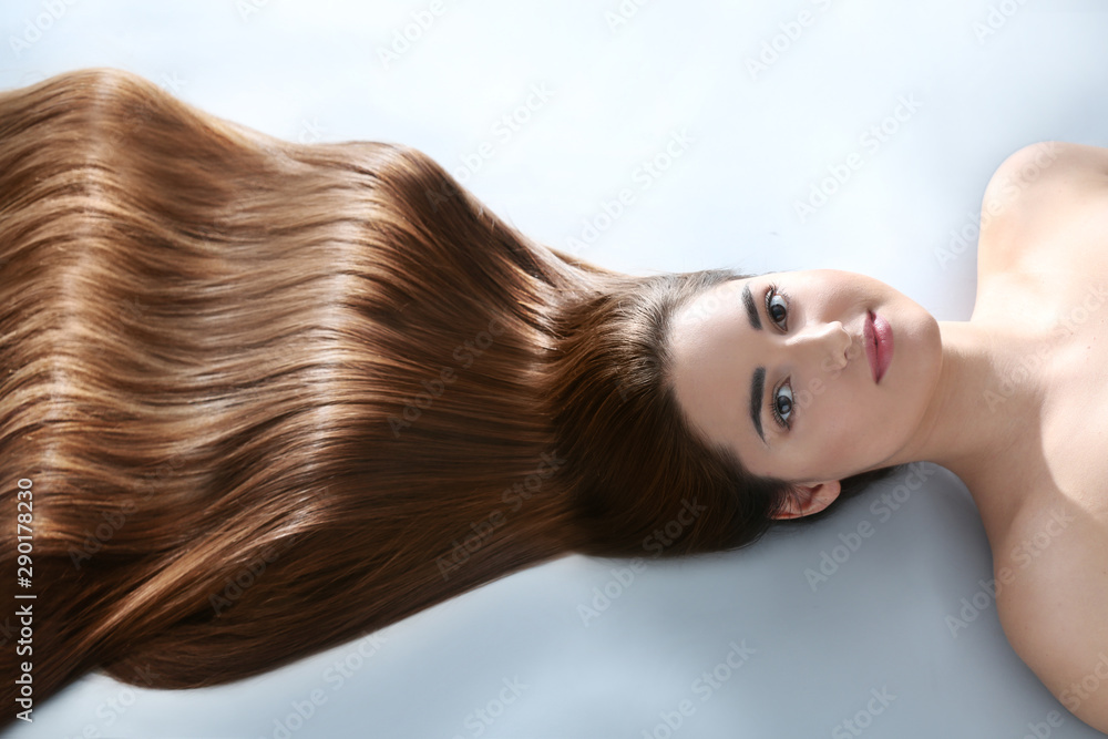Fototapeta Young woman with beautiful hair on light background