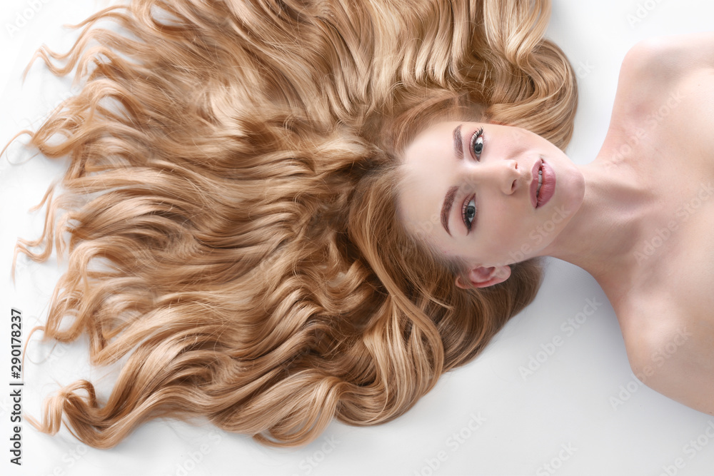 Fototapeta Young woman with beautiful curly hair on light background