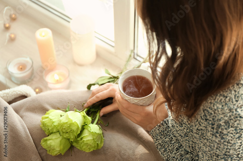 Cafe Woman with bouquet of beautiful green roses drinking tea near window