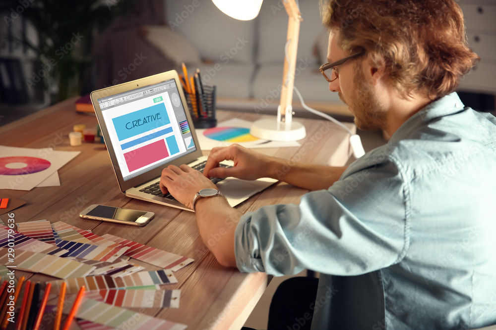 Fototapety, obrazy: Young designer working late in evening