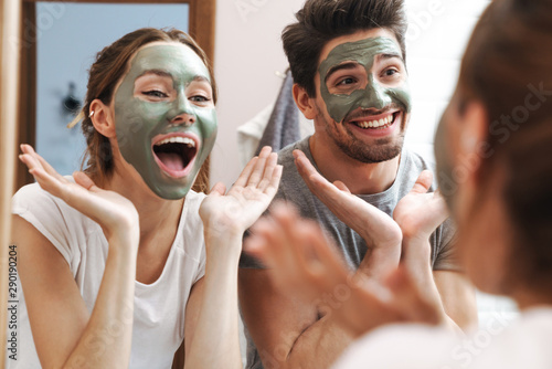 Cuadros en Lienzo  Image of joyful couple standing in bathroom with face mask