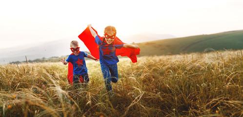 happy children boy and girl in costumes of superheroes in outdoor