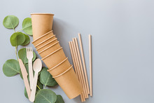 Eco Natural Paper Cups, Straws, Wooden Cutlery Flat Lay On Gray Background. Sustainable Lifestyle Concept. Zero Waste, Plastic Free Items. Stop Plastic Pollution. Top View, Overhead, Template, Mockup.